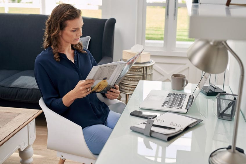 woman reading business magazine at home office desk